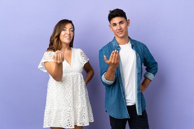 Молодая пара кавказской на фиолетовом, приглашая прийти с рукой.