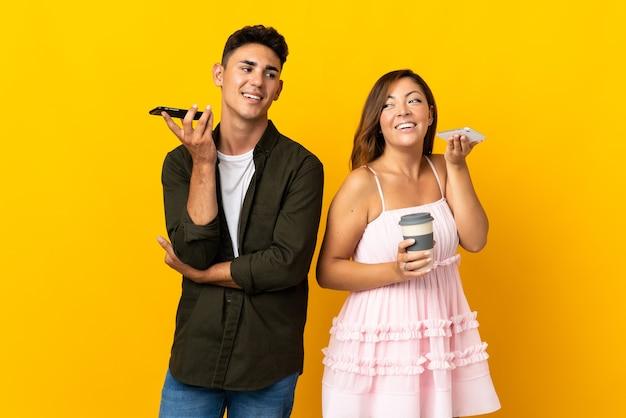 Молодая кавказская пара на желтом, отправляя голосовое сообщение или электронное письмо с мобильного телефона