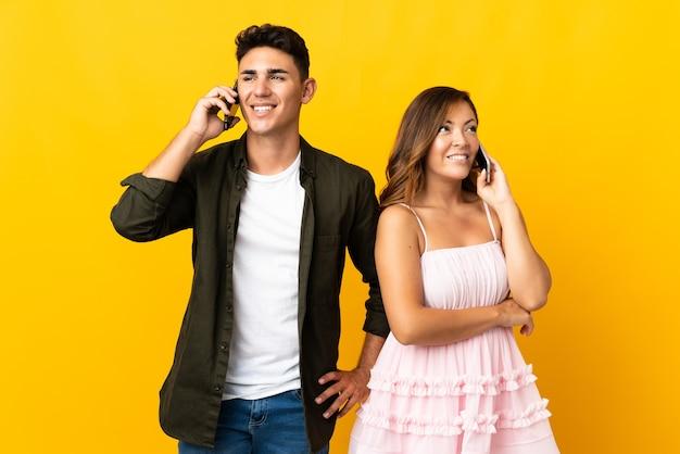 Молодая кавказская пара на желтом разговаривает по мобильному телефону