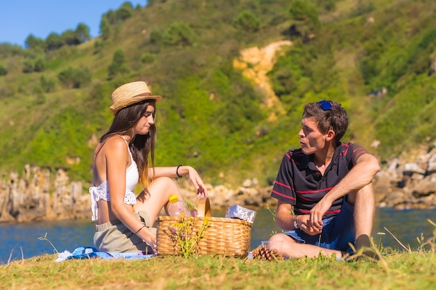 A young caucasian couple on the picnic in the mountains by the sea enjoying the heat