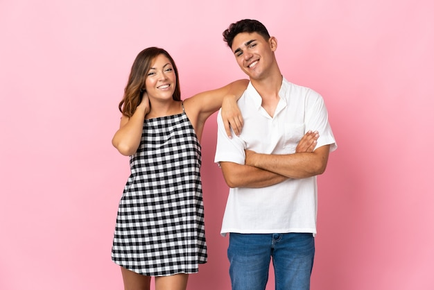 Young caucasian couple on pink happy and laughing