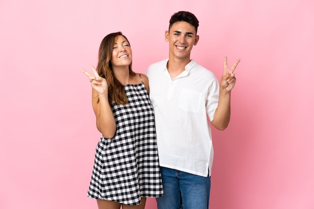 Young caucasian couple on pink smiling and showing victory sign