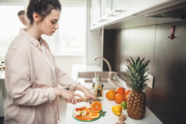 Молодая кавказская пара вместе готовит фруктовый салат на кухне, нарезая фрукты