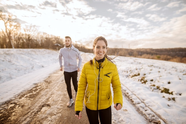 Young caucasian couple running together in nature in winter