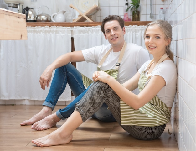 Молодая кавказская пара сидит и разговаривает на кухне