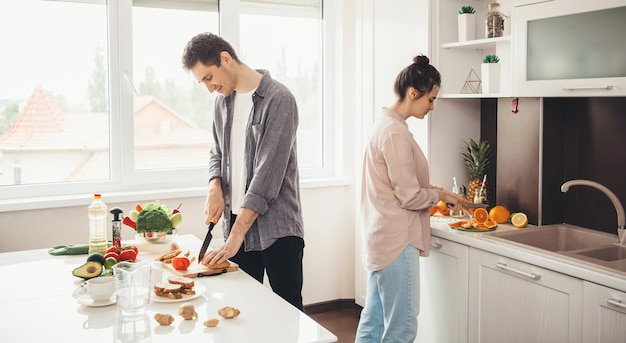 台所で果物をスライスし、一緒に朝食を準備する若い白人カップル