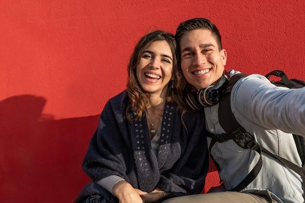 Молодая кавказская пара делает селфи фото смеясь. мужчина и женщина в повседневной одежде, путешественники или студенты. красная стена на фоне.