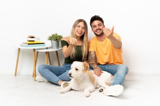 Молодая кавказская пара с собакой остается дома, приглашая прийти с рукой