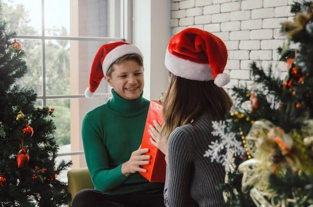 집에서 크리스마스 트리 축하와 여자 친구에게 크리스마스 선물 상자를주는 놀라운 빨간 산타 모자와 함께 젊은 백인 부부