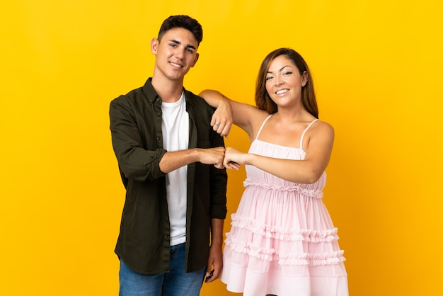 Young caucasian couple on yellow bumping fists