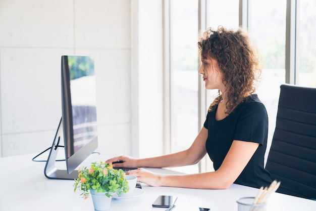 Young caucasian creative worker working on computer in office at home