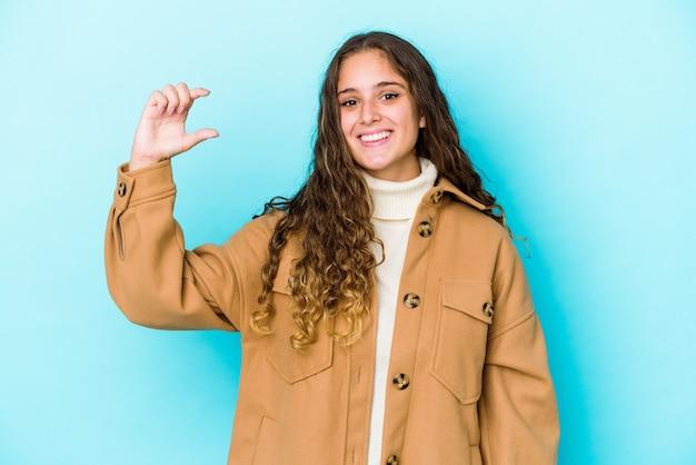 Молодая кавказская женщина с вьющимися волосами изолировала что-то маленькое с указательными пальцами, улыбаясь и уверенно.