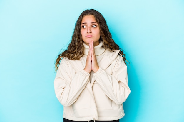 Молодая кавказская женщина с вьющимися волосами изолировала молящуюся, показывая преданность, религиозный человек, ищущий божественного вдохновения.