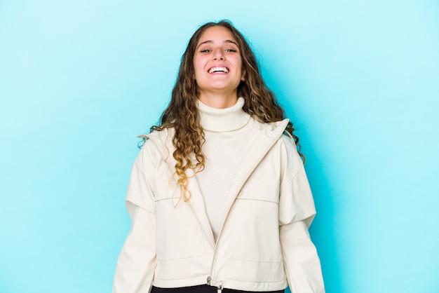 Молодая кавказская женщина с вьющимися волосами изолирована расслабленным и счастливым смехом, вытянув шею, показывая зубы