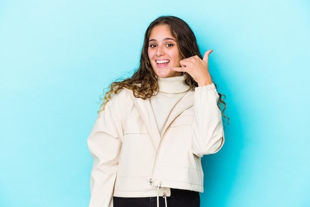 Молодая кавказская женщина вьющихся волос изолировала показывая жест звонка мобильного телефона с пальцами.