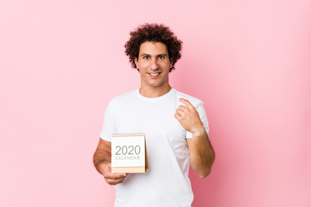 Young caucasian curly man holding a 2020 calendar pointing with finger at you as if inviting come closer.