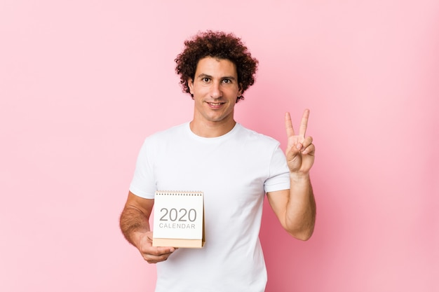 Young caucasian curly man holding a 2020 calendar showing number two with fingers.