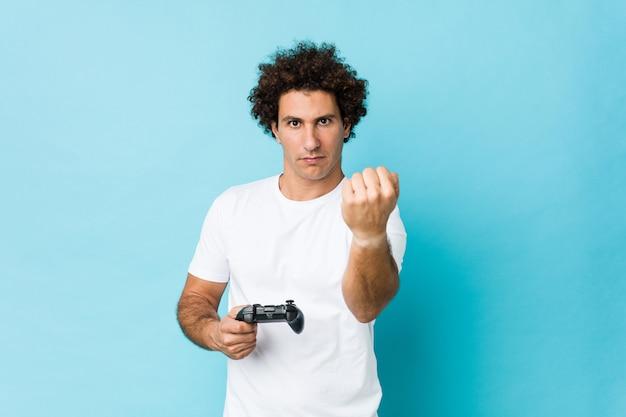 Молодой кавказский курчавый человек держа игровой контроллер показывая кулак к камере