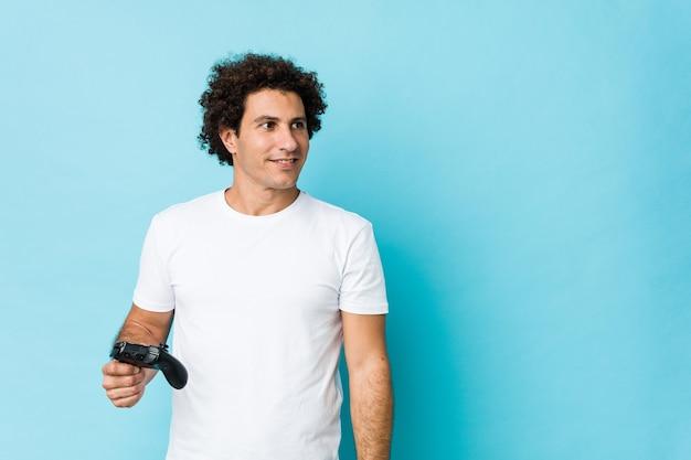 Молодой кавказский кудрявый человек, держащий игровой контроллер, уверенно улыбается со скрещенными руками.