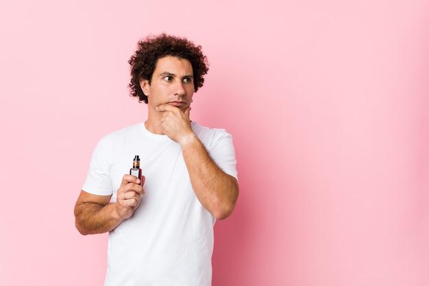 疑わしいと懐疑的な表現で横向きのアークを保持している若い白人の巻き毛の男。