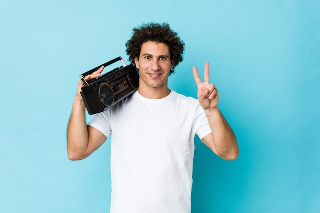 Young caucasian curly man holding a guetto blaster showing victory sign and smiling broadly.