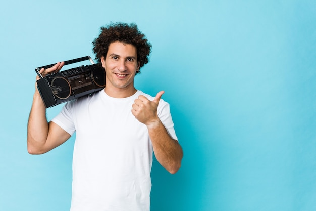Young caucasian curly man holding a guetto blaster