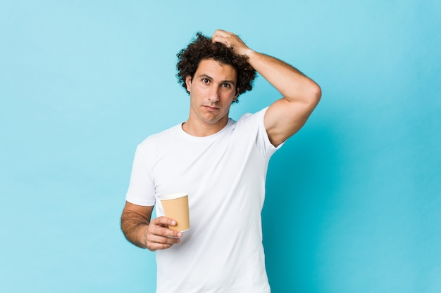 Young caucasian curly man holding a takeaway coffee being shocked, she has remembered important meeting.