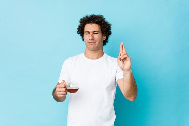 Young caucasian curly man holding a tea cup crossing fingers for having luck
