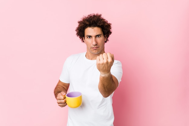 Young caucasian curly man holding a tea cup showing fist to camera, aggressive facial expression.