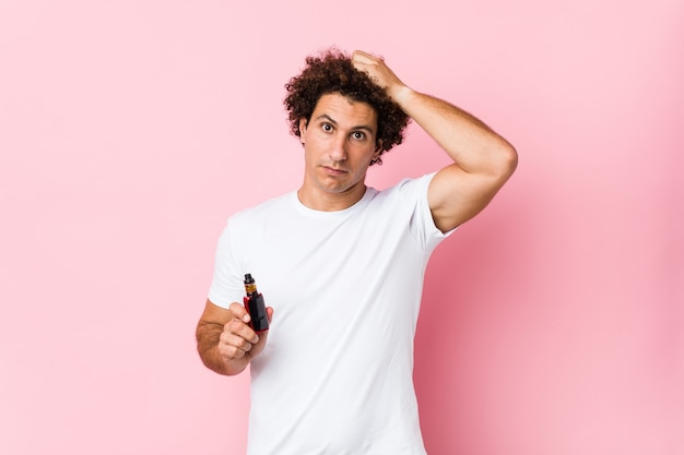 Young caucasian curly man holding a vape being shocked, she has remembered important meeting.