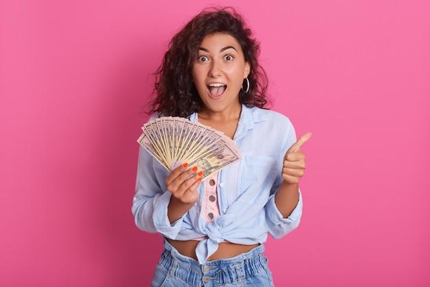 Молодая кавказская кудрявая женщина держит кучу банкнот позирует, изолированные на розовой стене, будучи счастливым и удивленным, стоит с большой улыбкой, показывая пальцем вверх пальцами,