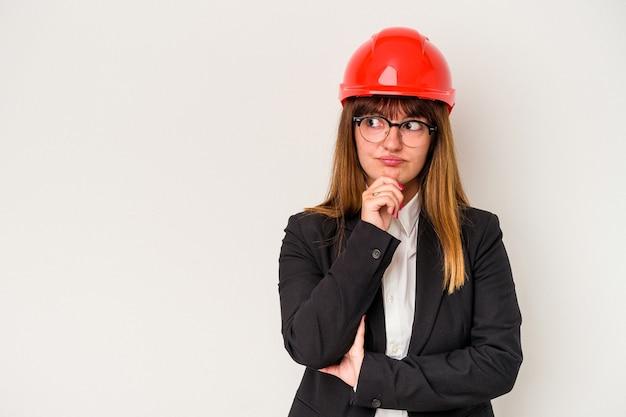 흰색 배경에 격리된 백인 매력적인 건축가 여성은 의심스럽고 회의적인 표정으로 옆을 바라보고 있습니다.