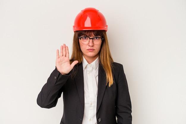 若い白人の曲がりくねった建築家の女性は、一時停止の標識を示して、あなたを防ぐために伸ばした手で立っている白い背景で隔離。