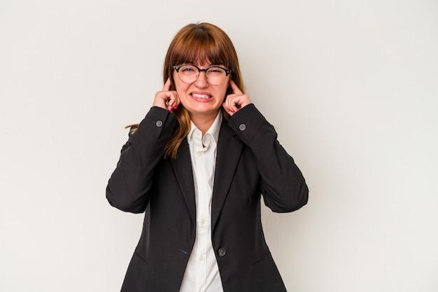 手で耳を覆う白い背景で隔離の若い白人の曲がりくねったビジネス女性。