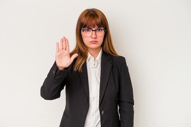 一時停止の標識を示している手を伸ばして立っている白い背景で隔離の若い白人の曲がりくねったビジネス女性は、あなたを防ぎます。