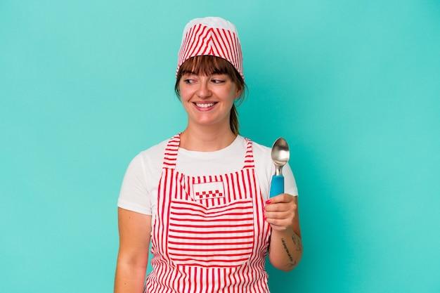 青い背景で隔離のスクープを保持している若い白人の曲線美のアイスクリームメーカーは、笑顔、陽気で楽しい脇に見えます。
