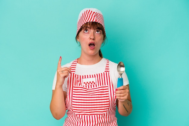 口を開けて逆さまを指している青い背景に分離されたスクープを保持している若い白人の曲がりくねったアイスクリームメーカー。