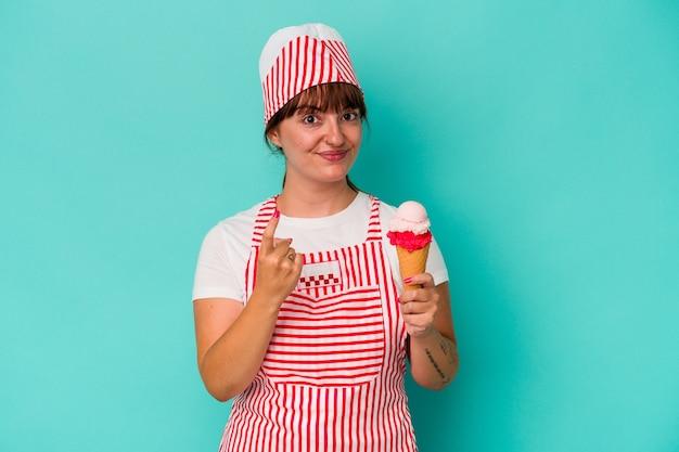 青い背景で隔離されたスクープを持っている若い白人の曲がりくねったアイスクリームメーカーは、招待が近づくようにあなたに指を指しています。
