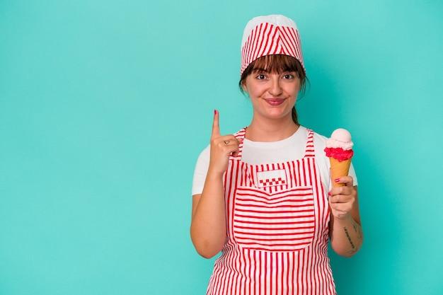 指でナンバーワンを示す青い背景で隔離のスクープを保持している若い白人の曲がりくねったアイスクリームメーカー。