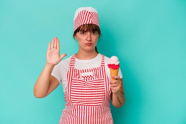 一時停止の標識を示す伸ばした手で立っている青い背景で隔離のスクープを保持している若い白人の曲がりくねったアイスクリームメーカーは、あなたを防ぎます。