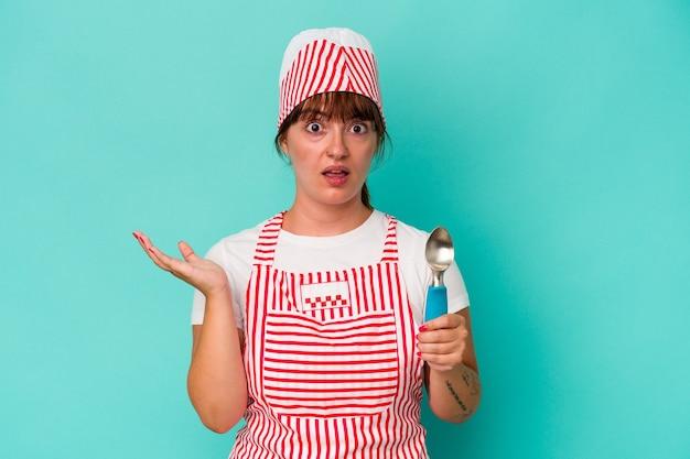 青い背景に分離されたスクープを保持している若い白人の曲線美のアイスクリームメーカーは驚きとショックを受けました。
