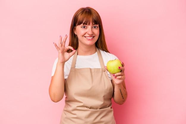 ピンクの背景に分離されたリンゴを持って自宅で料理をしている若い白人の曲線美の女性は陽気で自信を持って大丈夫なジェスチャーを示しています。