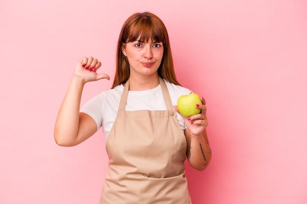 ピンクの背景に分離されたリンゴを持って自宅で料理をしている若い白人の曲線美の女性は、誇りと自信を持っています。