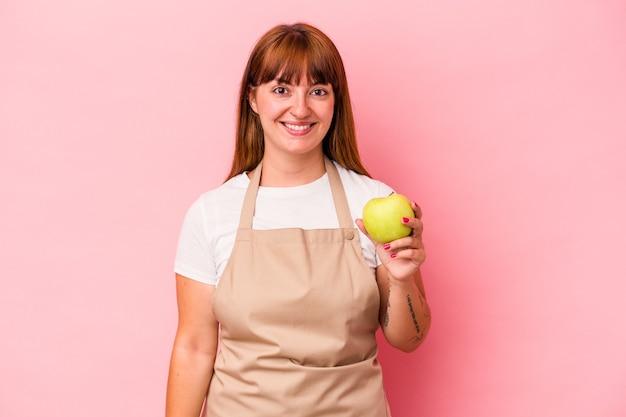 ピンクの背景に分離されたリンゴを持って家で料理をしている若い白人の曲がりくねった女性は幸せ、笑顔、陽気な。