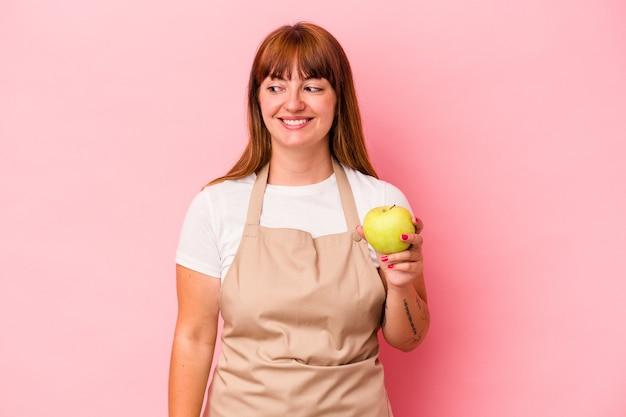 ピンクの背景に分離されたリンゴを持って自宅で料理をしている若い白人の曲がりくねった女性は、笑顔、陽気で楽しい脇に見えます。