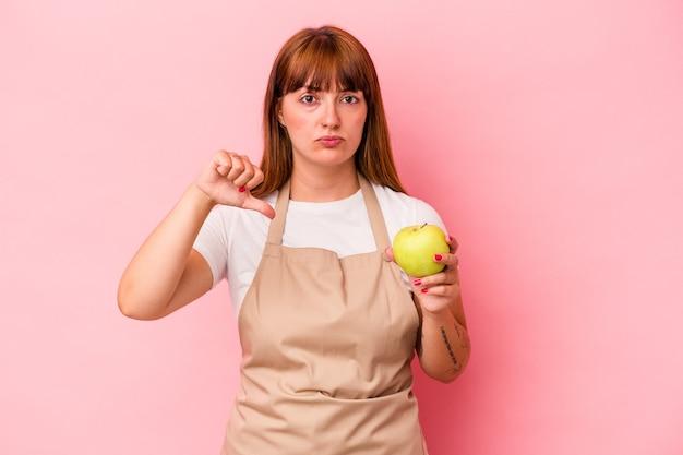 ピンクの背景に分離されたリンゴを持って自宅で料理をしている若い白人の曲線美の女性は、嫌いなジェスチャーを示し、親指を下に向けます。不一致の概念。