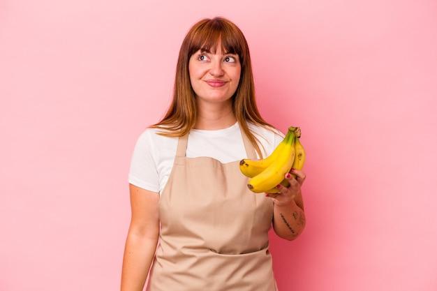 目標と目的を達成することを夢見てピンクの背景に分離されたバナナを保持している自宅で料理をする若い白人の曲線美の女性