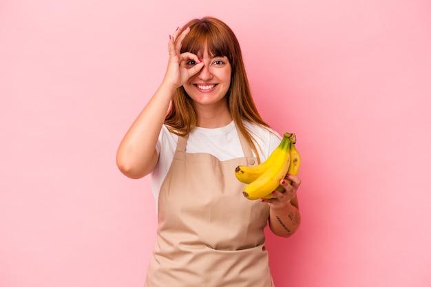 ピンクの背景に分離されたバナナを持って家で料理をしている若い白人の曲がりくねった女性は、目に大丈夫なジェスチャーを保ちながら興奮しています。