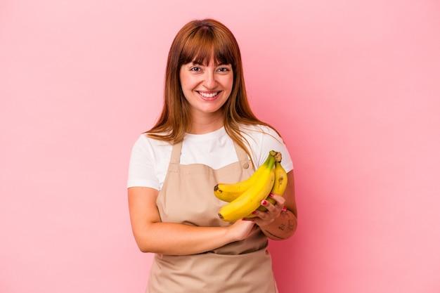笑って楽しんでピンクの背景に分離されたバナナを持って自宅で料理をしている若い白人の曲がりくねった女性。
