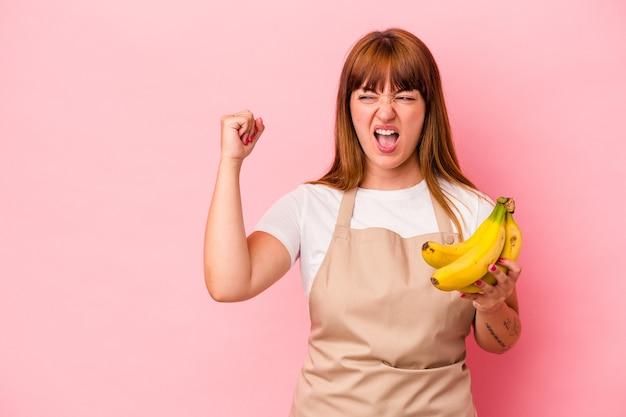 勝利、勝者のコンセプトの後に拳を上げるピンクの背景に分離されたバナナを持って自宅で料理をする若い白人の曲がりくねった女性。